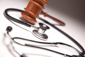 Medical Negligence, gavel and stethoscope on gradated background with selective focus.